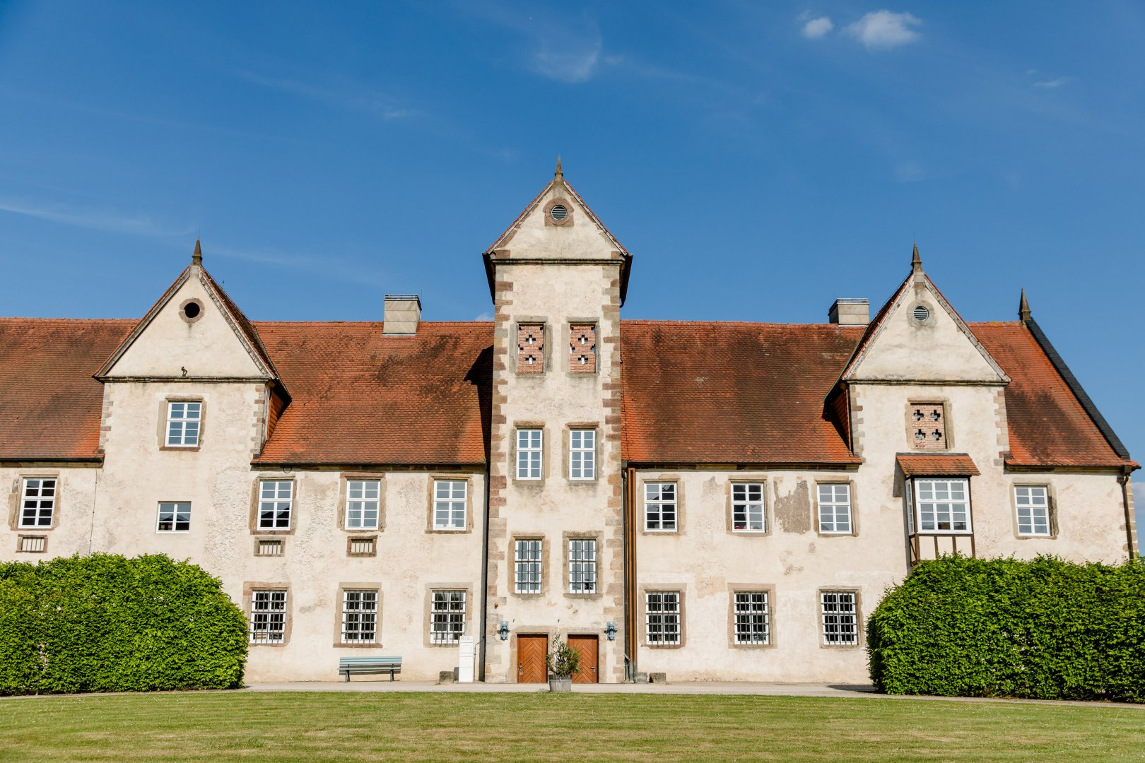 Property Building Estate Home House Château Manor house Architecture Real estate Mansion Facade Sky Roof Historic house Grass Tree Stately home Residential area Lawn Window Villa Turret Almshouse