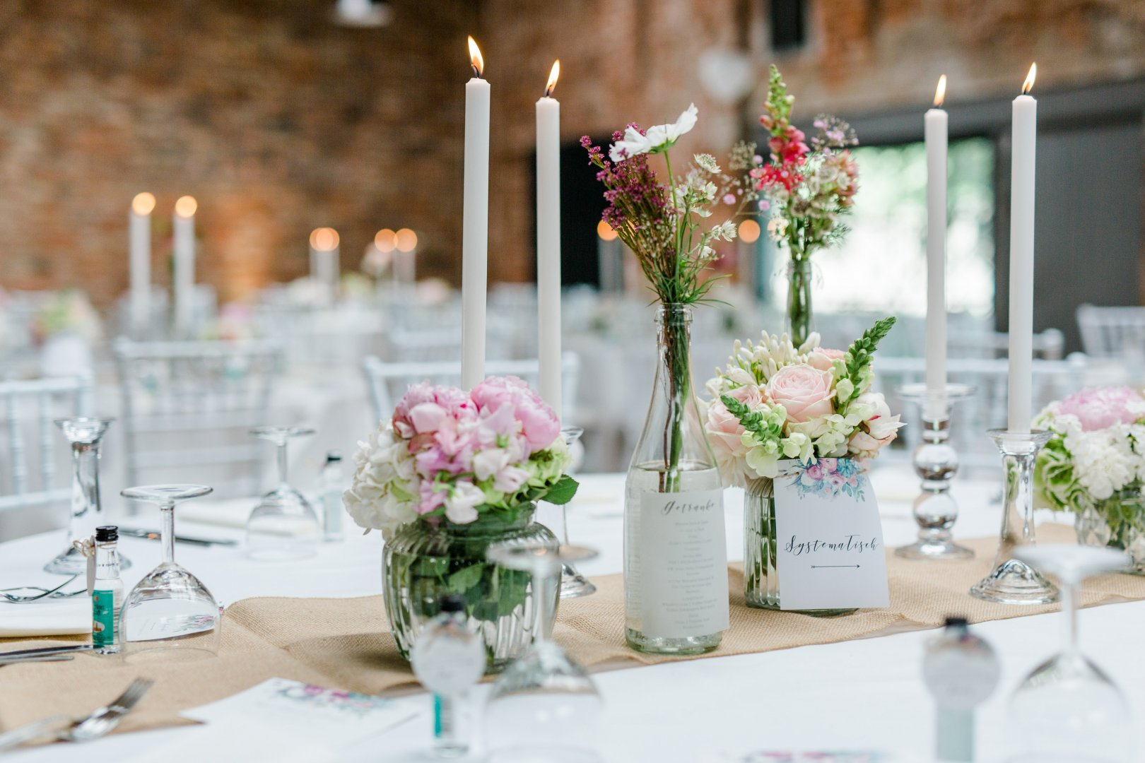 Decoration Centrepiece Flower Arranging Wedding banquet Flower Floristry Floral design Rehearsal dinner Pink Tableware Wedding reception Plant Candle Cut flowers Table Event Bouquet Interior design Artificial flower Party Room Function hall Banquet Ceremony Vase Interior design