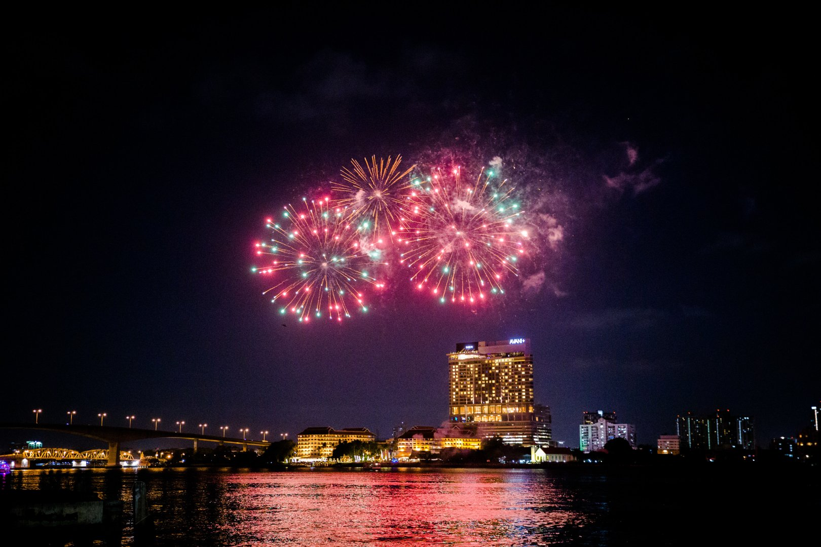 Fireworks Night Sky New Years Day Landmark Reflection Metropolitan area Midnight City Light Pink Lighting Atmospheric phenomenon Human settlement River Event Cityscape Darkness Holiday Urban area New year's eve Recreation Downtown Architecture New year Skyline Fête Metropolis Festival Cloud