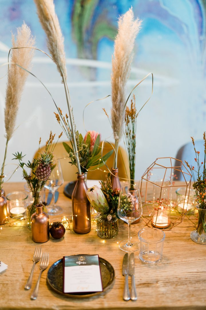 Feather Centrepiece Table Grass family Twig Champagne stemware Floral design Tableware Flower Arranging Plant Rehearsal dinner Glass Floristry Ceremony Branch Flower Drinkware Wildflower Interior design Brunch Still life photography