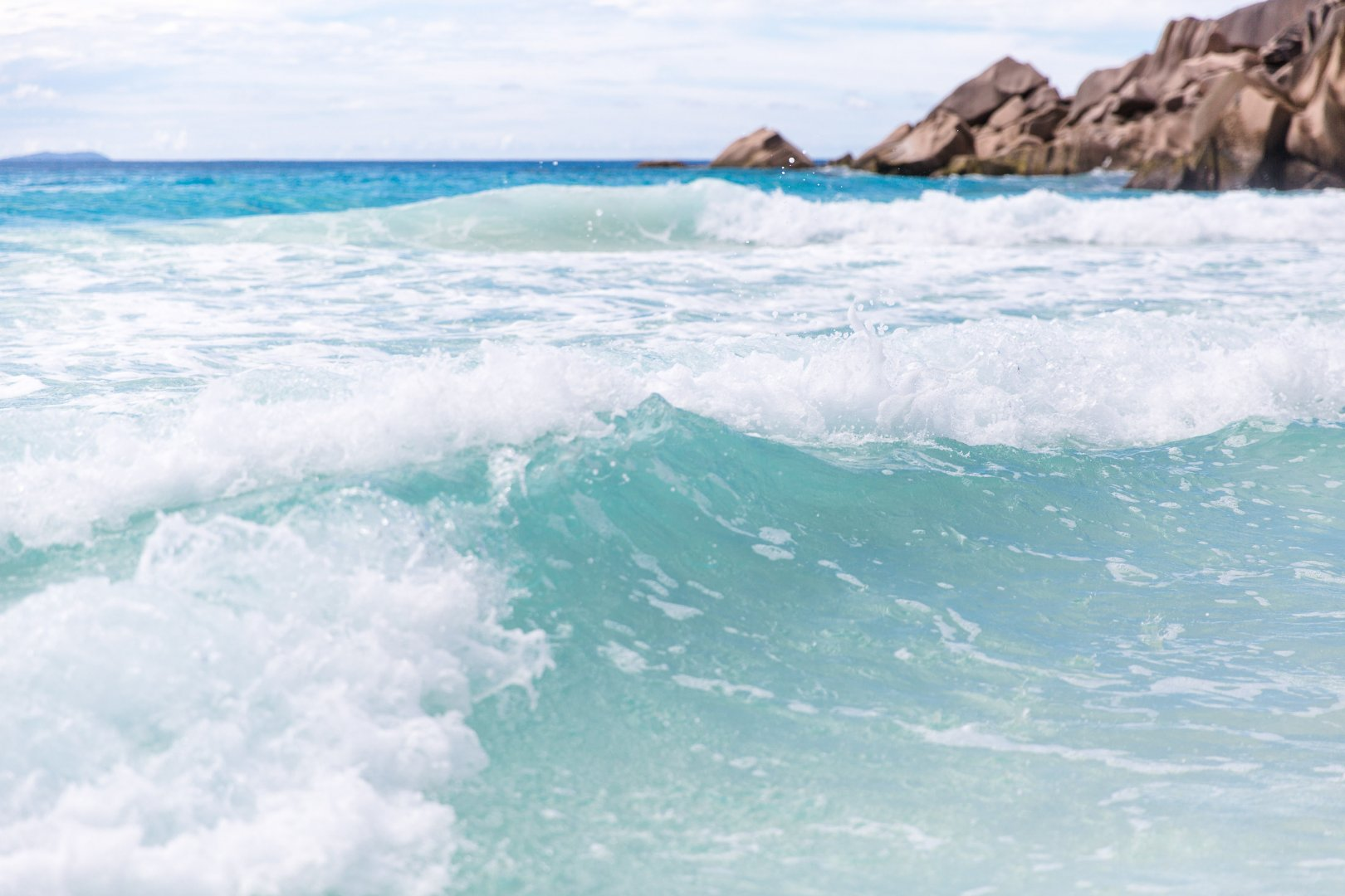 Wave Body of water Wind wave Ocean Sea Water Sky Coast Shore Water resources Coastal and oceanic landforms Tide Beach Surfing Bay Cliff Rock Surface water sports Vacation Cloud Landscape Tourism Terrain Tropics Wind Caribbean